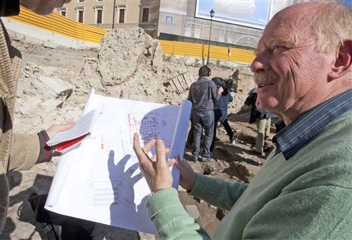 Italian archeologist Roberto Egidi points to a drawing near the remains of an ancient auditorium where scholars, politicians and poets held debates and lectures.