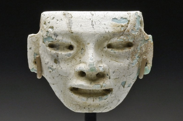 Pre-Columbian, Eastern Mexico, Ca 200 to 600 CE. Carved stone head, in what looks to be turquoise, now covered in deep white caliche (hardened deposit of calcium carbonate); with deep set, almond-shaped eyes, large lips open as if speaking and drilled ears. Custom stand. 20mm x 23mm. PROVENANCE: Ex-prominent Chicago, IL Collection acquired from Throckmorten Fine Arts. Authenticity Guaranteed
