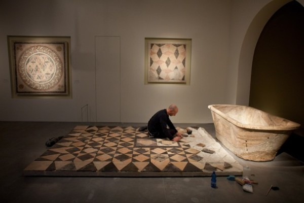 "Uriel Sinai/Getty Images -  A museum worker does preparatory work before the opening of the ""Herod the Great"" exhibition, at the Israel Museum this week in Jerusalem."