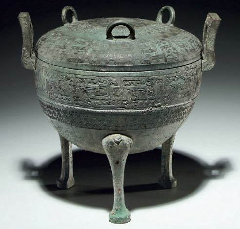 Lot 1130. A BRONZE RITUAL TRIPOD FOOD VESSEL AND COVER, DING WARRING STATES PERIOD, 5TH CENTURY BC (The Bronze ding is illustrated the pottery ding is not) Bronze ding 10 in. (25.4 cm.) high; pottery ding 10 in. (25.4 cm.) high (2) Estimate: $25,000-35,000