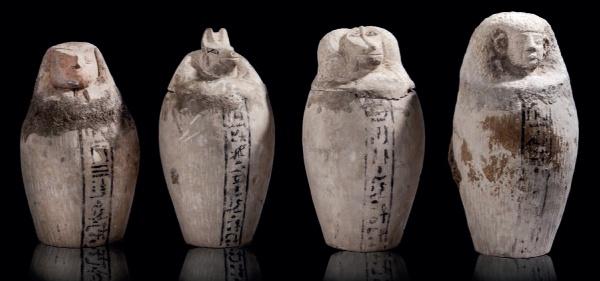Lot 35. Exceptionnel ensemble de quatre Vases Canopes, provenant du même mobilier funéraire d'une tombe de la basse époque. Pierre calcaire sculptée. Les bouchonssont à l'effigie des quatre FILS d'HORUS – AMSET à tête humaine contenant le foie, HÂPI à tête de babouin les poumons, DOUAMOUTEF à tête de chacal l'estomac, et QEBESENOUF à tête de faucon contenant les intestins. Sur chacun, une ligne verticale contenant d'inscription hiéroglyphique. Basse Epoque. Hauteur : 24,5 à 28,8 cm.  Estimate: €10,000-15,000