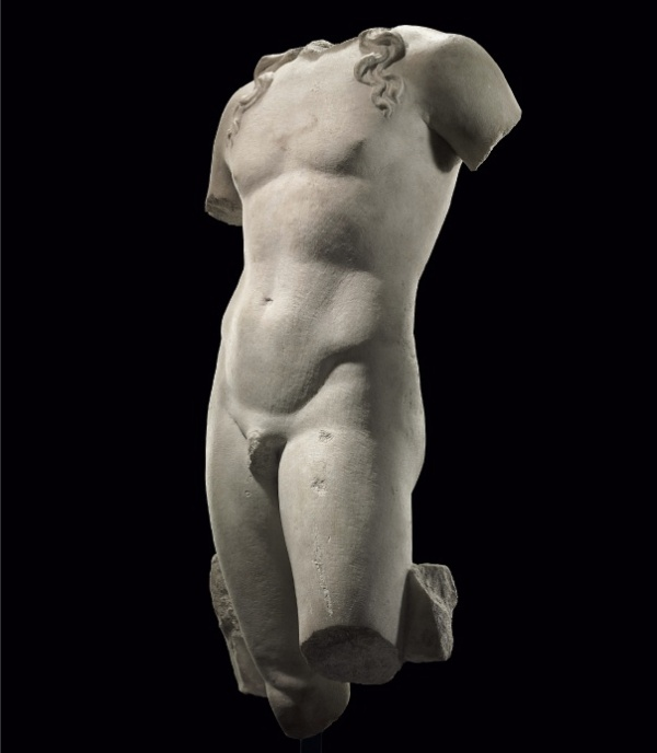 Lot 610. A ROMAN MARBLE TORSO OF APOLLO  CIRCA 1ST CENTURY B.C.-1ST CENTURY A.D.  Depicted lifesized, standing in contrapposto with his weight on his right leg, the left slightly advanced, with both arms lowered, the left pulled slightly back, the lithe figure with softly-modelled musculature, his long serpentine tendrils falling onto each shoulder, preserving a tree trunk support along the right thigh, and a smaller rectangular strut at the back of the left thigh 34½ in. (87.6 cm.) high  Estimate: $200,000-300,000. Provenance with Hosur Corporation, Kusnacht, Switzerland, 1989.