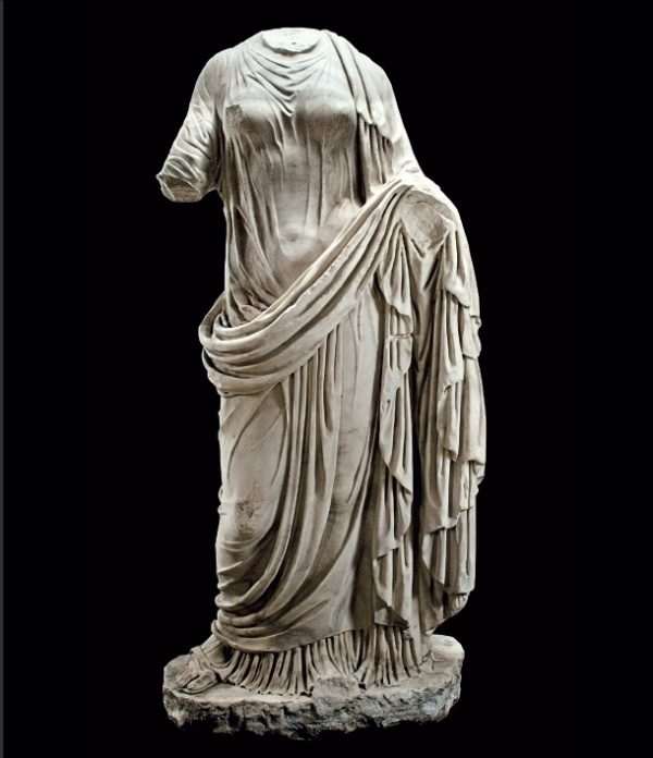 Lot 636. A ROMAN MARBLE DRAPED FEMALE  CIRCA 2ND CENTURY A.D.  Lifesized, depicted standing with her weight on her left leg, her right bent at the knee with the sandalled foot splayed, wearing a long-sleeved stola, buttoned along the right sleeve, the garment clinging to her body, revealing her voluptuous form beneath, her right arm extending out to the side, her left arm lowered and bent forward, with a heavy palla draped over her left shoulder, pulled in a diagonal across her right hip, up and over her left arm, and wrapped around her legs, falling in thick zigzags along her left side, its deep vertical folds defining her legs and contrasting with the pleats of the stola emerging below, on an integral plinth 57 in. (146 cm.) high  Estimate: $400,000-600,000. Provenance Private Collection, California. Anonymous sale; Butterfield & Butterfield, Los Angeles, 24-25 March 1998, lot 4387. Private Collection, Los Angeles. Anonymous sale; Bonhams, Los Angeles, 28 April 2008, lot 436w. with Phoenix Ancient Art, Geneva and New York, 2009 (Catalog no. 1, no. 12).