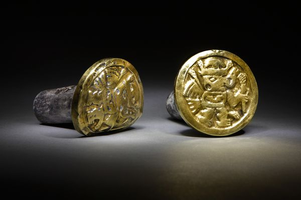 Images of winged, supernatural beings adorn a pair of heavy gold-and-silver ear ornaments that a high-ranking Wari woman wore to her grave in the newly discovered mausoleum at El Castillo de Huarmey in Peru. The Wari forged South America's earliest empire between 700 and 1000 A.D., and their Andean capital boasted a population greater than that of Paris at the time. Today, Peru's Minister of Culture will officially announce the discovery of the first unlooted Wari imperial tomb by a team of Polish and Peruvian researchers. In all, the archaeological team has found the remains of 63 individuals, including three Wari queens. Photograph by Daniel Giannoni.