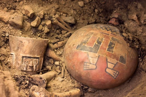 As archaeologists dug in one side chamber, they unearthed the remains of a Wari queen and several regal offerings, including a brilliantly painted ceramic flask (right) and an alabaster drinking cup (left). Photograph by Patrycja Przadka Giersz.
