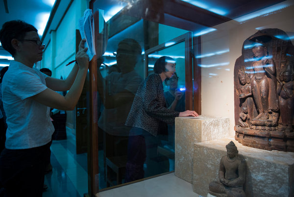 Melissa Chiu, center, museum director of the Asia Society, near a sculpture of Buddha descending from heaven at a museum in Bagan, Myanmar. Adam Dean for The New York Times.