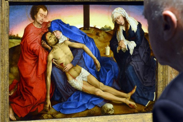 """A visitor looks at """"Pieta"""" at the opening of the exhibition entitled """"The heritage of Rogier van der Weyden"""" presenting the works of early Flemish painter Rogier van der Weyden at the Royal Museums of Fine Arts of Belgium in Brussels on October 10, 2013. AFP PHOTO/BELGA/BENOIT DOPPAGNE."""