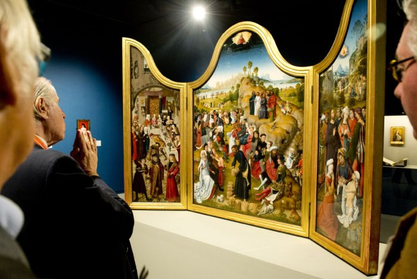 """Visitors look at """"Triptych with the miracles of Christ"""" by early Flemish painter Rogier van der Weyden at the opening of the exhibition entitled """"The heritage of Rogier van der Weyden"""" presenting his works at the Royal Museums of Fine Arts of Belgium in Brussels on October 10, 2013. AFP PHOTO/BELGA/BENOIT DOPPAGNE"""