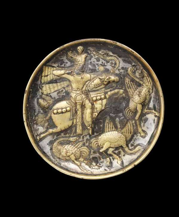 Lot 107. A Sasanian silver-gilt royal hunting scene plate  Iran, circa early 4th Century A.D. The interior decorated in relief, the figural scene with gilding and finely incised details, depicting a king, thought to be Hormizd II, riding a horse at flying gallop to right, the king wearing a crown in the form of a winged eagle surmounted with a globe, with three rippling streamers flying out behind, wearing a chest halter over a belted tunic, and trousers with pleated edging, wearing a quiver at his right hip, decorated with a wavy palmette tendril and a rosette above, a beribboned sword hilt on his left, seated astride the horse with a dotted cross-hatched saddle blanket, a pair of incised balloons fly out behind, a rippling ribbon attached to its bridle with a ribbed globe above, wearing a harness ornamented with large bosses, its tail elaborately tied, the king drawing a bow, taking aim at a fleeing ostrich or great bustard in front, two shot birds below, one collapsed with an arrow through its turned neck, the other shot through its breast, the plate on a ring foot, the base with a dotted Pahlavi inscription mentioning the weight, and two monograms (23.3cm) diameter; 791.9g weight FOOTNOTES Provenance: Private collection, Switzerland, acquired between 2002-2005. European private collection, UK and Switzerland, formed in the 1970s and 1980s. Estimate: £150,000-250,000 ($250,000-420,000).