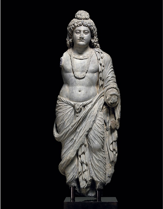 Lot 1600. AN IMPORTANT AND IMPRESSIVE GREY SCHIST FIGURE OF A BODHISATTVA  GANDHARA, 2ND/3RD CENTURY  The bodhisattva is standing in a relaxed pose, with his weight resting on his right leg and his left slightly bent. He is clad in a dhoti tied at the waist and a sanghati with cascading folds of drapery. The bodhisattva is adorned with a close-fitting torque and braided necklace with a crescent-shaped amulet. His handsome face is very finely carved with a bow-shaped mouth, aquiline nose and almond-shaped eyes, the forehead centered by a raised urna. The hair is arranged in thick, wavy locks and tied over the ushnisha. 38¼ in. (97 cm.) high  Estimate: $600,000-800,000 Provenance Private collection, Japan, by 1985. Private collection, New York, acquired at Christie's New York, 17 October 2001, lot 4.