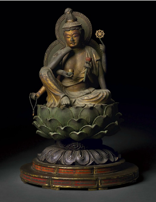 "Lot 1616. A POLYCHROME- AND GILDED-WOOD FIGURE OF NYOIRIN KANNON, ""THE BODHISATTVA WHO GRANTS DESIRES"" JAPAN, KAMAKURA PERIOD, WITH DOCUMENTATION DATED 1304 CE  The ""bodhisattva who grants desires"" (Sanskrit, Cintamani-chakra-Avalokiteshvara Bodhisattva) is carved from a single block of wood, for the body, and six separately carved and inserted partially replaced arms on a separately assembled lotiform throne. The figure is shown seated in the posture of ""royal ease"" with the left leg folded horizontally to expose the sole of the foot, on which the right foot rests.The right thigh supports the elbow of the one of the deity's six arms, the hand touching the right cheek of the inclined head in a gesture of contemplation. The lower of the three right arms holds a rosary and the upper cups, as if to extend, a lotus jewel, the nyoi hoju (cintamani) that bestows wishes. The main left arm steadies the figure on the lotus throne. The raised left arm bent at the elbow has a hand with four clasped fingers and index finger pointed upward, which supports another attribute, the Wheel of the Law, or rin, forming a syllable of the deity's name. The third left hand clasps the stalk of a blossoming lotus, symbolic of spontaneous generation (the lotus reproduces from its matrix not soil), the purity and perfection of the Buddha and the mercy and compassion associated with Kannon (Avalokiteshvara). The delicate features of the face, painted black with gold overlayer, have a black mustache and forehead scallop above the inlaid glass urna between the arched brows. The glass eyes are white with black pupils. Pendulous earlobes and elaborate black coiffure frame the face. The hair on the back of the head is carved in narrow vertical lobes. The figure is clothed in a skirt that ripples onto the lap and legs in gentle pleats and in a shoulder scarf, carved to the middle of the back in a series of wide, U-shaped pleats. The drapery shows areas of meticulous gilded diaperwork, particularly evident on the edges of the scarf, central fold and over the knees of the robe. The arms are black with slight traces of gold coloration. The lotus throne is comprised of a bracket-footed double plinth in the outline of a lotus flower that is embellished on the edges with flower reserves in red, black and gold pigment below a support of lotus lappets applied with black lacquer. The uppermost plinth supporting the figure is carved with overlapping green lotus leaves detailed with gold veins. The reverses of the central lacquered support and upper green lotus support are carved smooth and the back surface of the lotus support is cut with a small rectangle to accommodate the peg of a separate mandorla. Figure 8 1/8 in. (20.5cm.) high; figure with pedestal 14½ in. (36.9 cm.) high With accompanying shari (interior relics of stones wrapped in paper symbolizing the cremated remains of the Buddha) and votive documentation mounted on two handscrolls and with later mandorla and lacquered-wood shrine. Estimate: $200,000-300,000. NO PROVENANCE"