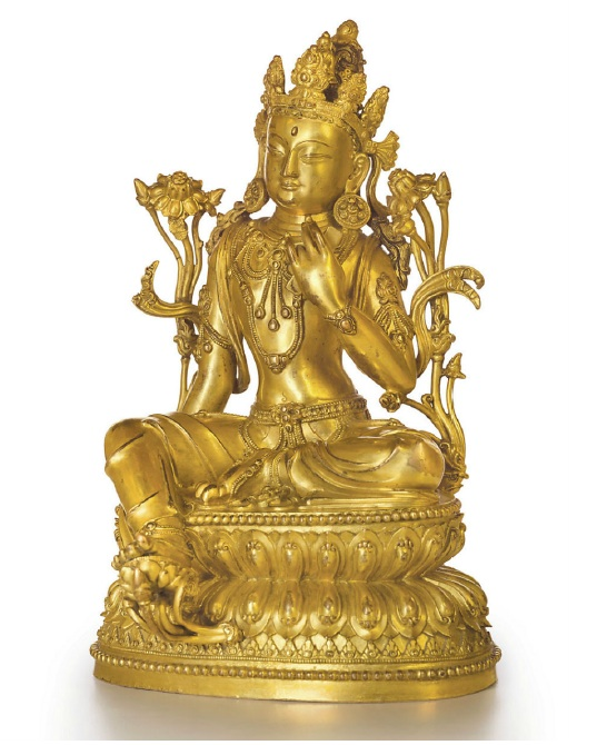 "Lot 1622. A RARE AND SUPERBLY CAST GILT-BRONZE FIGURE OF AVALOKITESHVARA  CHINA, MING DYNASTY, YONGLE SIX-CHARACTER MARK INSCRIBED IN A LINE AND OF THE PERIOD (1403-1425) The bodhisattva is shown seated in lalitasana with the right foot supported on a lotus stem that projects from the front of the double-lotus base just above a rare, additional narrow band of circle-centered leaves. The right hand, which rests on the edge of the base, holds one of the two stems that rise to the shoulders from the sides of the base, while the raised left hand holds the Book of Wisdom. The graceful figure wears an elegantly draped dhoti secured with a beaded, festoon-hung sash, beaded necklaces, armlets, large circular earrings and a ribbon-tied tiara with eight foliate points that surrounds a seated figure of Amitabha Buddha and the artfully arranged chignon. The reign mark, Da Ming Yongle nian shi, ""Bestowed in the Great Ming Yongle reign,"" is inscribed in a line at the front of the base. The figure is richly gilded, and the base is sealed with a plate inscribed with a double vajra. 8¾ in. (22.3 cm.) high  Estimate: $600,000-800,000. Provenance Christie's New York, 21 March 2001, lot 88."