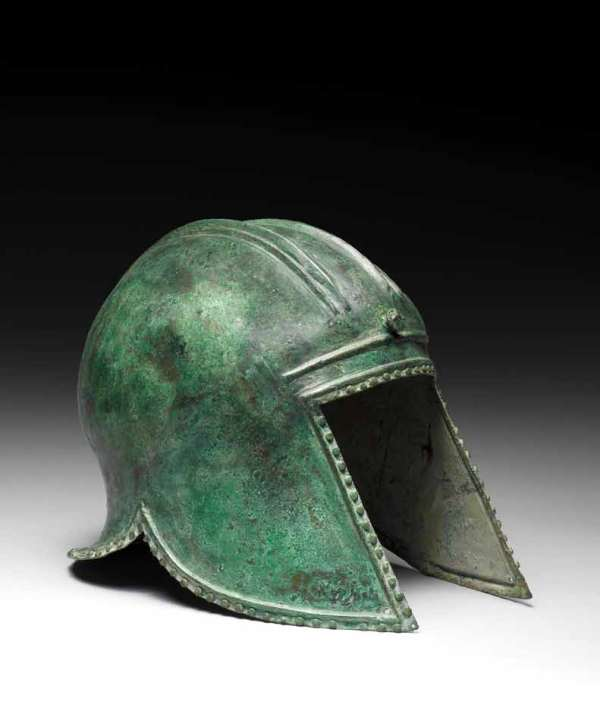 Lot 5. A Greek bronze Illyrian helmet  Circa 6th-5th Century B.C. The domed helmet with a pair of raised double parallel ridges, each with smaller ridges at the outer edge, with a central frontal tang and loop at the back for attachment of a crest, with an everted rear flange and long pointed cheekpieces perforated at the forward tip, edged with a border of studs, 9in (23cm) high FOOTNOTES Provenance: English private collection, acquired in the early 1990s on the UK art market. Estimate: £10,000-15,000 ($17,000-25,000).