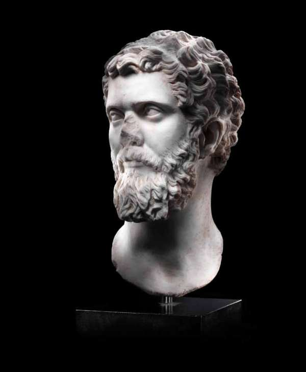 Lot 67. A Roman marble portrait head of the Emperor Septimius Severus  Circa 194 A.D.  Slightly over-lifesized, depicted with his head turned to his right, his thick curling hair and beard with drilled detail, the beard characteristically full and long with ringlets at the chin and a thick moustache at the upper lip, his eyebrows incised above large eyes with articulated pupils gazing upward, the strong neck designed to be set into a composite statue, 16¼in (41.3cm) high, mounted FOOTNOTES Provenance: American private collection, California. Christie's New York, 11 December 2003, lot 232. European private collection, acquired in the 1980s. Estimate: £120,000-150,000 ($200,000-250,000).