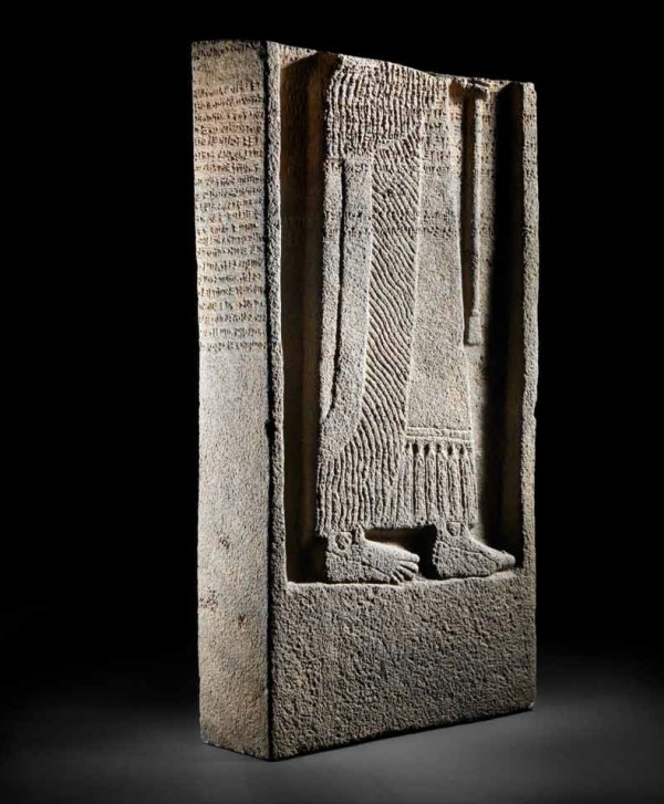 Lot 99. A monumental Neo-Assyrian black basalt royal stele of Adad-nerari III of Assyria  Circa 805-797 B.C. Comprising the lower two-thirds of the stele of rectangular cross-section, the front carved in high relief with a standing figure of the king in prayer, depicted in profile from the waist down, shown wearing a long fringed robe, with bare feet, holding a staff before him, the neat regular cuneiform text inscribed across the body of the king is preserved with the beginnings of lines 9-10 and lines 11-20 in their entirety, each line separated by horizontal rulings, with several lines continuing onto the raised border. 54in (137.5cm) high; 29½in (75cm) wide; 10½in (27cm) deep FOOTNOTES Provenance: Private collection, Geneva, Switzerland, given as a gift from father to son in the 1960s. Estimate: £600,000-800,000 ($1-1.3 million).