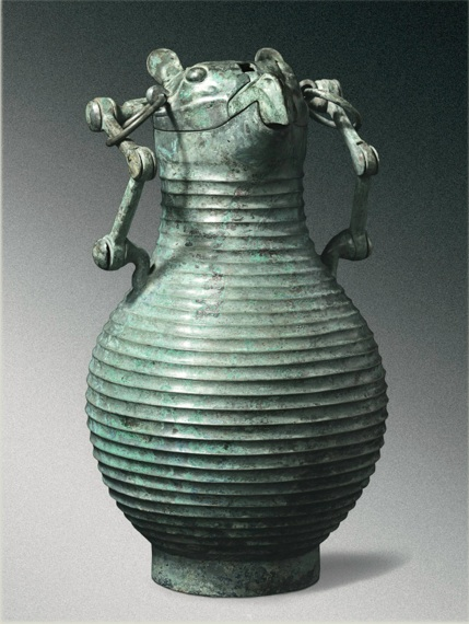 Lot 18. A VERY RARE AND IMPORTANT BRONZE OWL-HEADED RITUAL WINE VESSEL (HU) EARLY EASTERN ZHOU DYNASTY, 8TH-7TH CENTURY BC the stoutly cast pear-shaped body encircled by thirty horizontal grooves and supported on a straight ring foot, underneath a plain neck tapering on one end to a short channeled spout, the cover shaped as the head of a beaked raptor, with large eyes gazing upwards, two upright tab-shaped ears set in a shallow scrolled recess and the sharp down-curved beak separately hinged to the center of the mask, further set with a pair of loops supporting two large rings linked to a high swing handle made of movable sections, the lower-most sections secured by  a pair of nail-like knobs issuing from the shoulders, connected to the middle section by rotating hinge-like devices, in turn joined with a single yoke-shaped section over the top by the same devices as the lower-most joint, the interior of the cover engraved with a nine-character inscription, the patination of overall olive-green color, with light malachite encrustations   Height 18 1/4  in., 46.5 cm Estimate: $4-6 million.