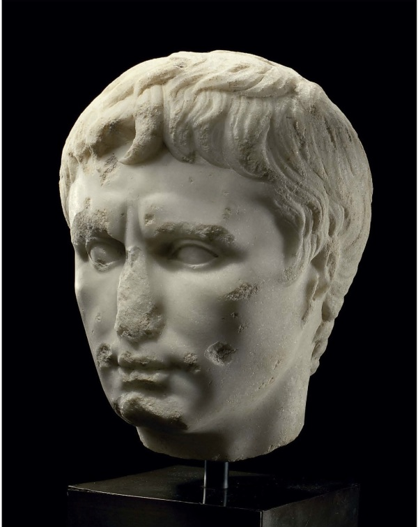 Lot 114. A ROMAN MARBLE PORTRAIT HEAD OF THE EMPEROR AUGUSTUS  CIRCA LATE 1ST CENTURY B.C.-EARLY 1ST CENTURY A.D.  Over-lifesized, depicted with finely-modelled features, his oval face with strong cheekbones, the fleshy bow-shaped mouth with the lips pressed together, dimpled at the corners, the philtrum indicated, the naso-labial folds subtly portrayed, his almond-shaped convex eyes unarticulated and slightly recessed, two small diagonal lines extending above the bridge of his nose accentuating his knitted brow, a single shallow crease across the broad forehead, the layered hair composed of a mass of short comma-shaped locks, with the three characteristic locks at the center of his forehead, two parted at the center and one to his right, a single lock curving forward before each ear 12½ in. (31.8 cm.) high  Estimate: $200,000-250,000. Click on image to enlarge. Provenance Enrico Serranti and Giovanna LoMoro, New York and New Jersey, acquired in 1981. with Fortuna Fine Arts, New York, 1999. Antiquities, Christie's, New York, 8 June 2004, lot 57.