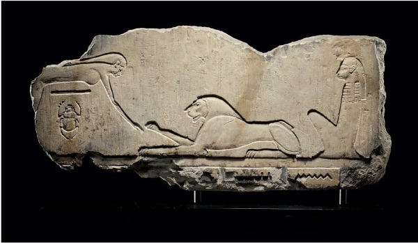 Lot 30. AN EGYPTIAN LIMESTONE RELIEF  PTOLEMAIC PERIOD, 304-30 B.C.  Sculpted in sunk relief, the sky goddess Nut to the left arching over a horizontal line representing Geb, the earth god, and the god Khepri, in the form of a scarab beetle, a lion to the right with its right forepaw raised, representing Horakhty, and Isis seated to the right, looking left, all on a groundline, the upper portion of a hieroglyphic inscription below 19 in. (48.2 cm.) wide  Estimate: $20,000-30,000 Click on image to enlarge.