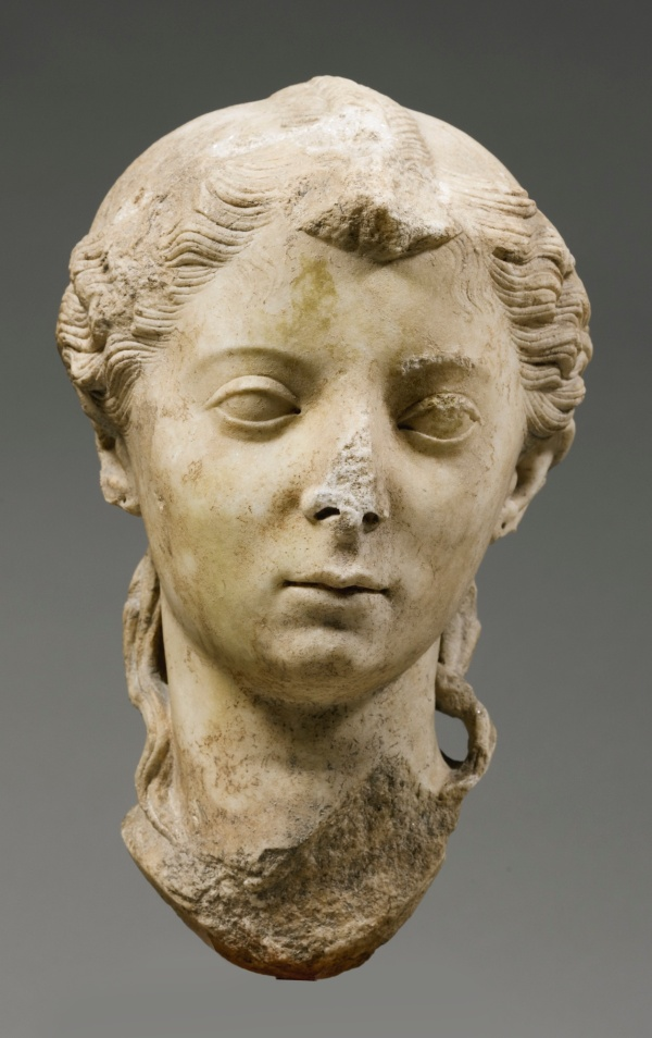 Lot 34. A MARBLE PORTRAIT HEAD OF A GIRL, ROMAN IMPERIAL, AUGUSTAN, 27 B.C.-A.D. 14 the neck carved for insertion into a statue, turned to her left, her face with delicate bow-shaped lips and large wide-set eyes under slightly arched eyebrows, her finely-carved hair parted in the center, bound in an invisible fillet, brushed in wavy locks over the sides, arranged in a nodus with central braid behind, tied in a broad braided chignon in back, and falling in long locks over the sides of the neck, finely engraved curls escaping over the forehead. Height 11 3/4 in. 29.8 cm. Estimate: $800,000-1,200,000. Click on image to enlarge.