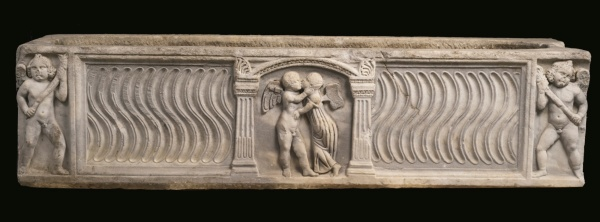 Lot 39. A MARBLE STRIGILLATED SARCOPHAGUS WITH EROS AND PSYCHE, ROMAN IMPERIAL, SECOND QUARTER OF THE 3RD CENTURY A.D. of rectangular form, carved in front at each end with an erote holding a torch, the central panel decorated within an architectural frame with Eros and Psyche embracing, each of the short sides carved with crossed shields. 19 1/2 by 79 3/8 by 23 1/8 in. 49.5 by 201.6 by 58.7 cm. Estimate: $60,000-90,000. Click on image to enlarge.