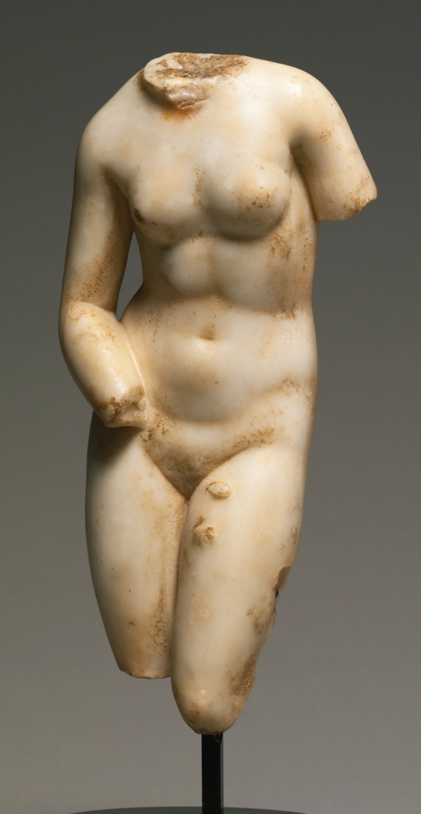 Lot 5. A MARBLE TORSO OF APHRODITE, ROMAN IMPERIAL, CIRCA 1ST CENTURY A.D. inspired by the Aphrodite of Knidos by Praxiteles, circa 350 B.C., the goddess standing with her weight on the right leg and bending forward slightly at the waist, her right forearm resting on her hip, the iron dowel on the left leg for attachment to a missing support. 13 1/4 in. 33.7 cm. Estimate: $80,000-120,000. Click on image to enlarge.