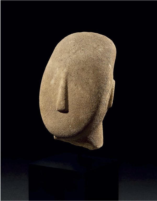 "Lot 60. A CYCLADIC MARBLE HEAD  EARLY SPEDOS VARIETY, EARLY CYCLADIC II, CIRCA 2600-2500 B.C.  From a large reclining figure, with a thick neck, the lyre-shaped head with a rounded chin and broad cheeks, the long triangular nose well centered, the convex face with a high sloping forehead tapering toward the top and terminating in a sharp-edged flat oval, the ears modelled in relief and indented at their centers, with traces of pigment ""ghosts"" for the eyes 5 in. (12.7 cm.) high  Estimate: $150,000-250,000. Click on image to enlarge. Provenance with Uraeus, Paris, prior to 1980."