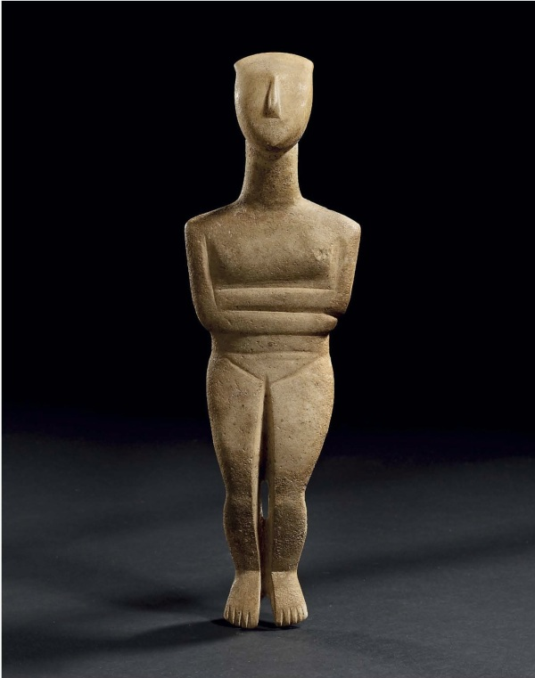 Lot 64. A CYCLADIC MARBLE RECLINING FEMALE FIGURE  EARLY SPEDOS VARIETY, EARLY CYCLADIC II, CIRCA 2600-2500 B.C.  The lyre-shaped head with a slender, well-centered nose, the neck elongated, the shoulders sloping, with small breasts, the arms folded right below left, the inguinal lines of the incised pubic triangle bisected by the upper end of the deep cleft which divides the legs, denoting the genitalia, the spine delineated by a shallow groove, the feet angled down, the toes articulated 10 in. (25.4 cm.) high Estimate: $200,000-300,000. Provenance with N. Koutoulakis, Paris, 1976.