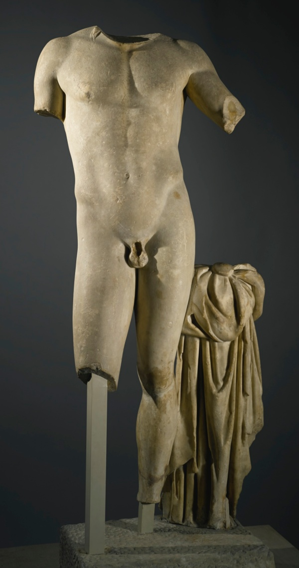 Lot 9. A MARBLE FIGURE OF APOLLO, ROMAN IMPERIAL, PROBABLY HADRIANIC, CIRCA 130 A.D. after a Greek original of circa 460 B.C., the god standing in a majestic attitude with his weight on the left leg, his right leg advanced and left arm raised, a strand of hair falling onto his right shoulder, his cloak draped over the support with long deeply carved folds, remains of his boot on the back of the left ankle. Height 59 in. 150 cm. Estimate: $200,000-300,000. Click on image to enlarge.