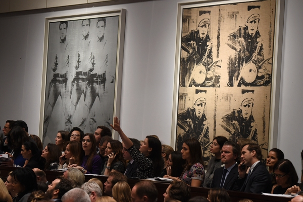 "Andy Warhol's ""Triple Elvis"" (L) and Four Marlons (R) are displayed during Christie's Post-War and Contemporary Art evening sale November 12, 2014 in New York. AFP PHOTO/Don Emmert.  Click on image to enlarge."