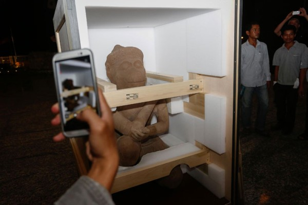 A statue of the Hindu monkey god Hanuman is received by officials at Phnom Penh International Airport Sunday night. After being looted from the KohKer temple complex in Preah Vihear province, the statue spent 33 years at the Cleveland Museum of Art in the US before being returned to Cambodia on Sunday. (Siv Channa/The Cambodia Daily)