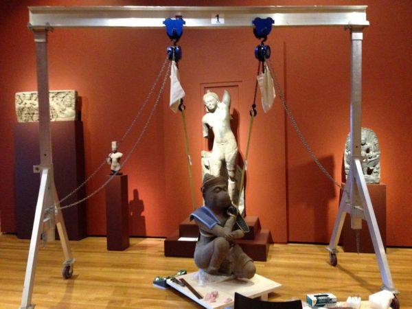 Technicians at the Cleveland Museum of Art used a harness and pulleys in the new West Wing galleries in December, 2013, to make a mold of the base of the Hanuman sculpture used to explore whether it was looted from a site in Cambodia. Click on image to enlarge.
